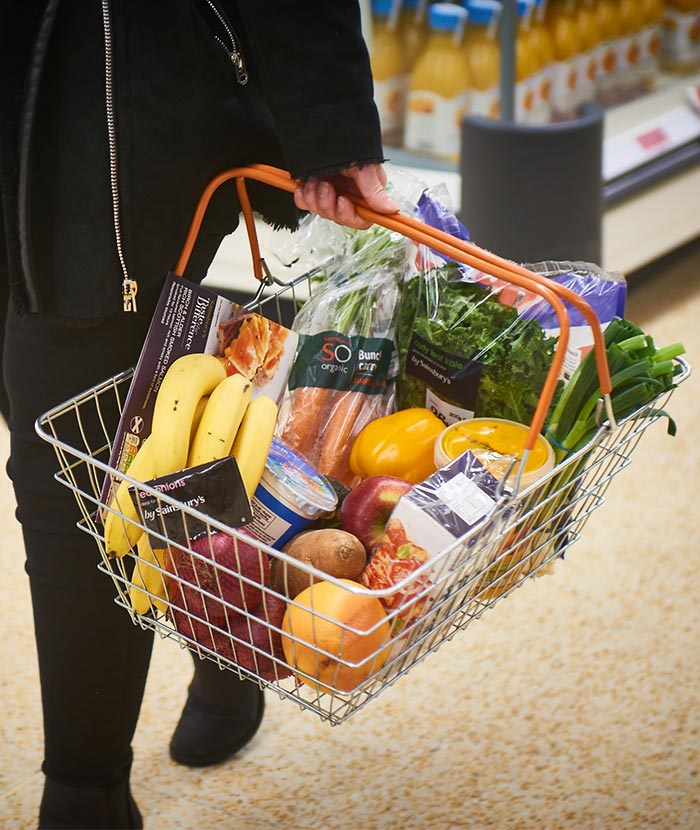 A healthy basket of fruit, vegetables and groceries being carried by a Sainsbury's customer